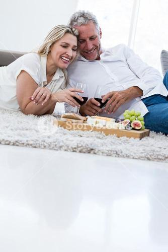 Smiling couple with red wine and food while lying on rug