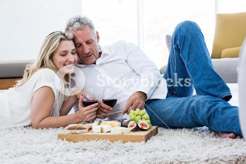 Cheerful couple with red wine and food while lying on rug