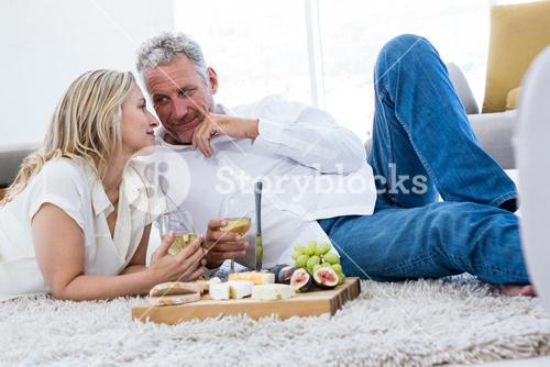 Romantic couple with white wine and food while lying on rug