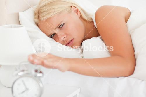 Cute woman awaken by an alarmclock