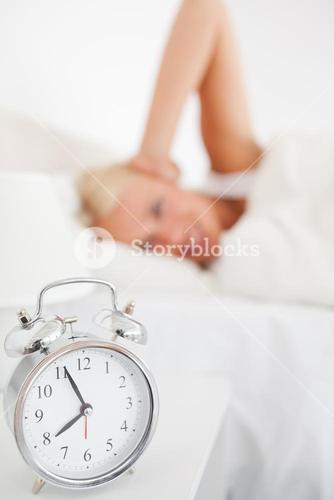 Alarmclock waking up a woman