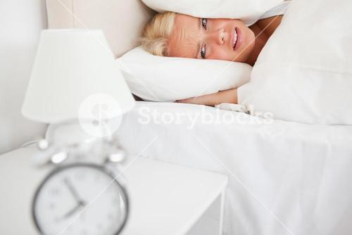 Tired woman hidding her head in a pillow while the alarmclock is ringing