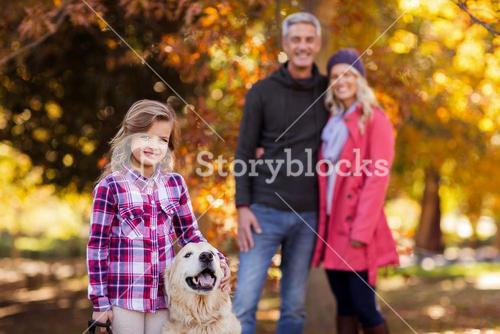 Girl with dog while parents standing at park