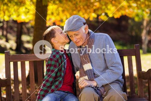 Grandson whispering to grandfather at park