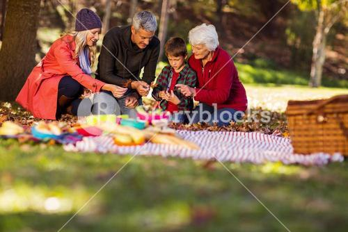 Family holding autumn leaves at park