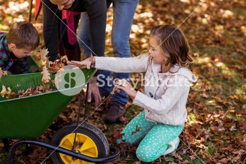 Children picking up autumn leaves with parents