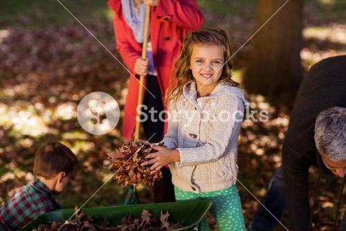 Girl picking up autumn leaves with family