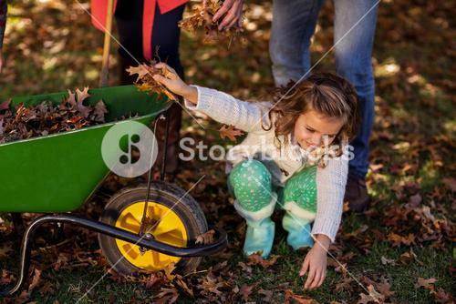 Girl picking up autumn leaves at park