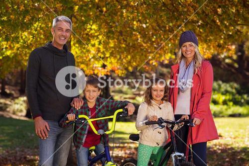 Children riding bicycles with parents at park