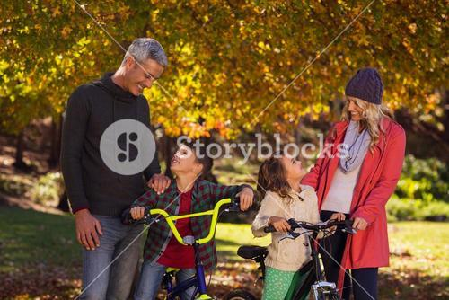 Happy children riding bicycles with parents