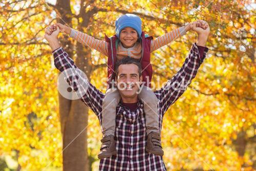 Happy father carrying son on shoulder at park