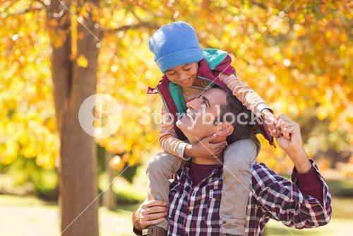 Cheerful father carrying son on shoulder at park