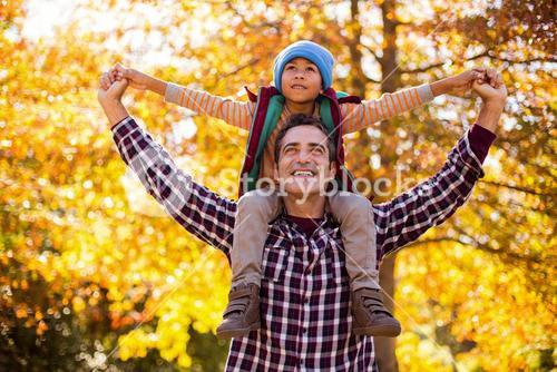 Father carrying son on shoulder against autumn trees