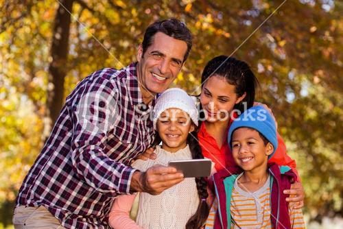 Man holding mobile phone with family at park