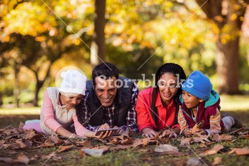 Happy family looking at mobile phone at park