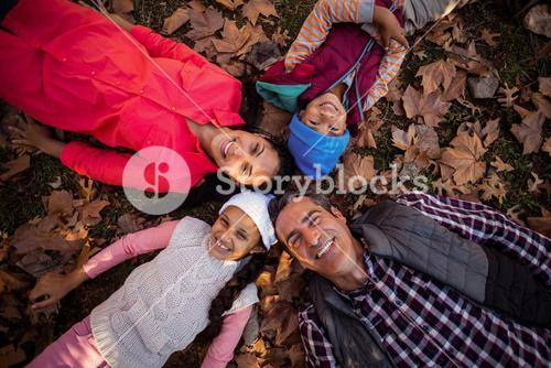 Happy family forming huddle while lying on field