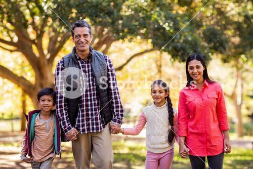 Portrait of family holding hands at park