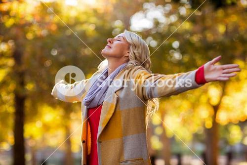 Woman standing with arms outstretched against autumn trees