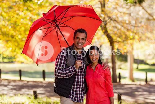Portrait of couple holding umbrella