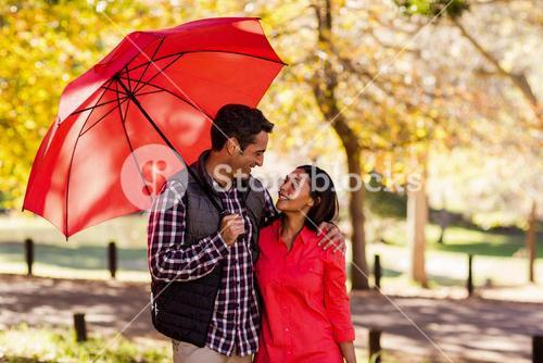 Couple holding umbrella at park