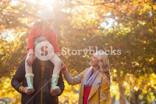 Father carrying daughter on shoulder while standing at park