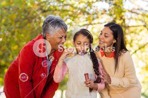 Multi-generation family blowing bubbles at park