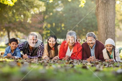 Portrait of family lying on front at park