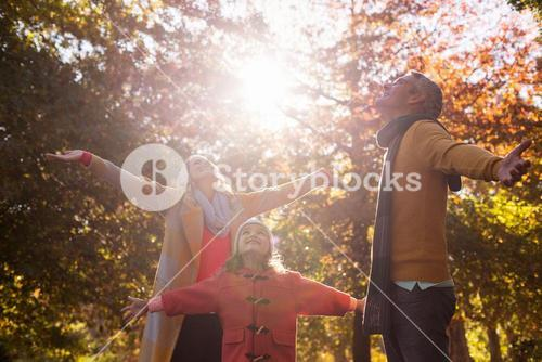 Family with arms outstretched against trees