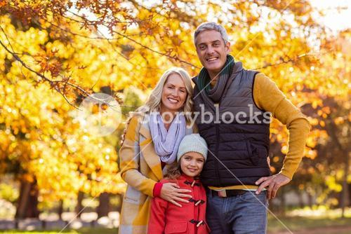 Portrait of happy family at park during autumn