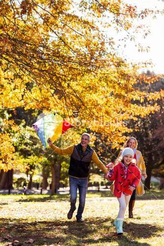 Family playing at park with kite