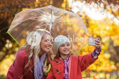 Girl taking selfie with mother at park