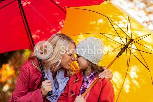 Cheerful mother and daughter with umbrella at park