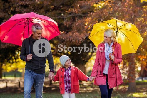 Cheerful parents with daughter at park