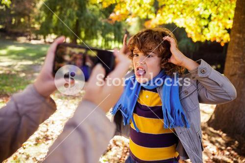 Cropped image of girl photographing boy making face in park
