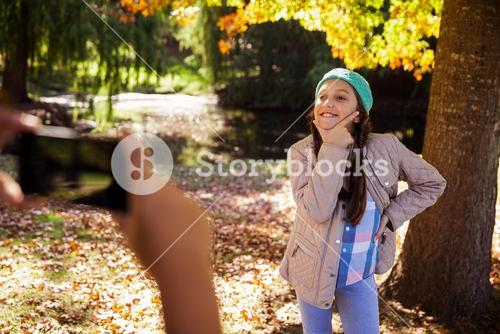 Cropped image of boy photographing girl in park