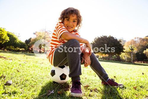 Portrait of smiling boy sitting on soccer ball