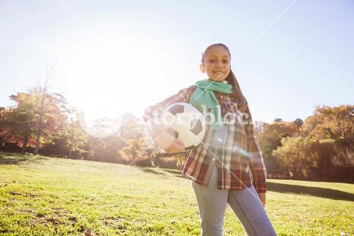 Low angle portrait of smiling girl holding soccer ball in park