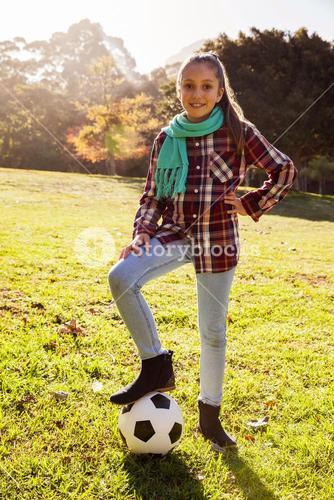 Portrait of smiling girl with soccer ball in park