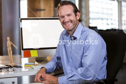 Smiling businessman sitting by computer desk
