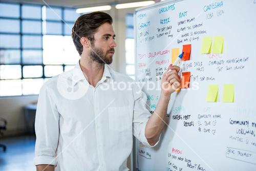 Businessman pointing on sticky note