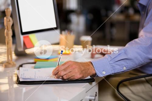 Businessman writing on paper at computer desk