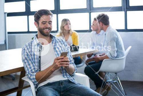 Creative businessman using cellphone by table