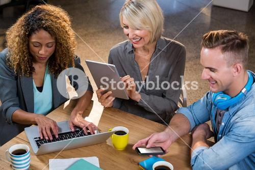 Creative business people using technologies at table