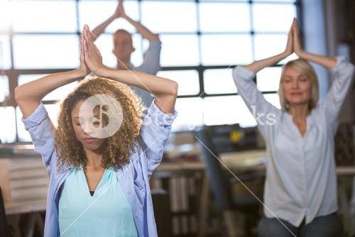 Creative business people practicing yoga
