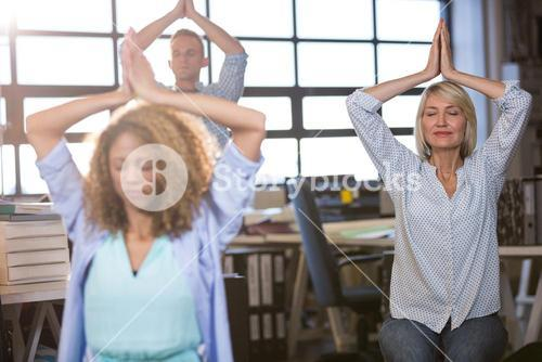 Businesswoman practicing yoga with colleagues