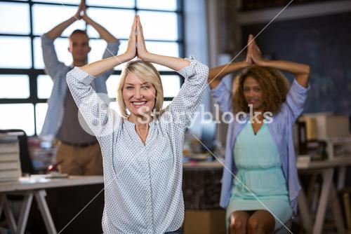 Businesswoman practicing yoga with coworkers