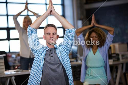 Businessman practicing yoga with coworkers