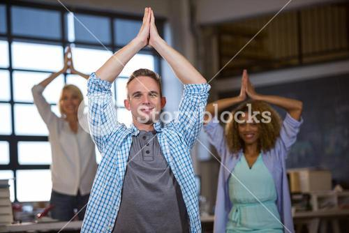 Business people smiling while practicing yoga