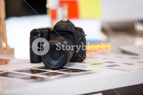 Camera on photographs at desk