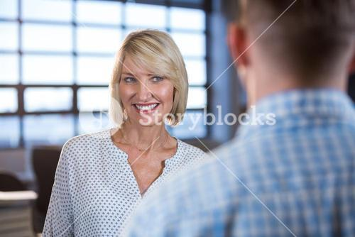 Businesswoman standing in front of male colleague